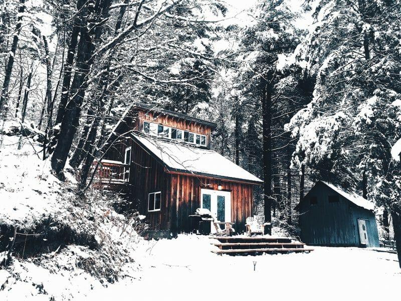 Casă în pădure pe timp de iarnă